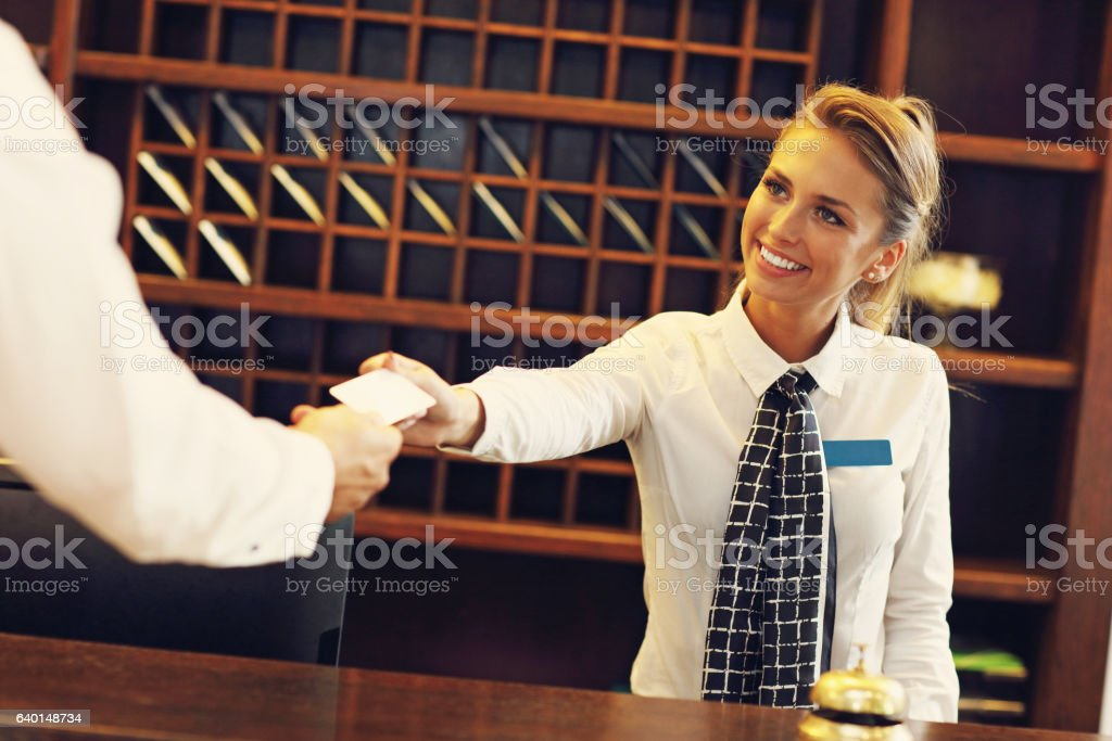 Pretty receptionist giving key card stock photo