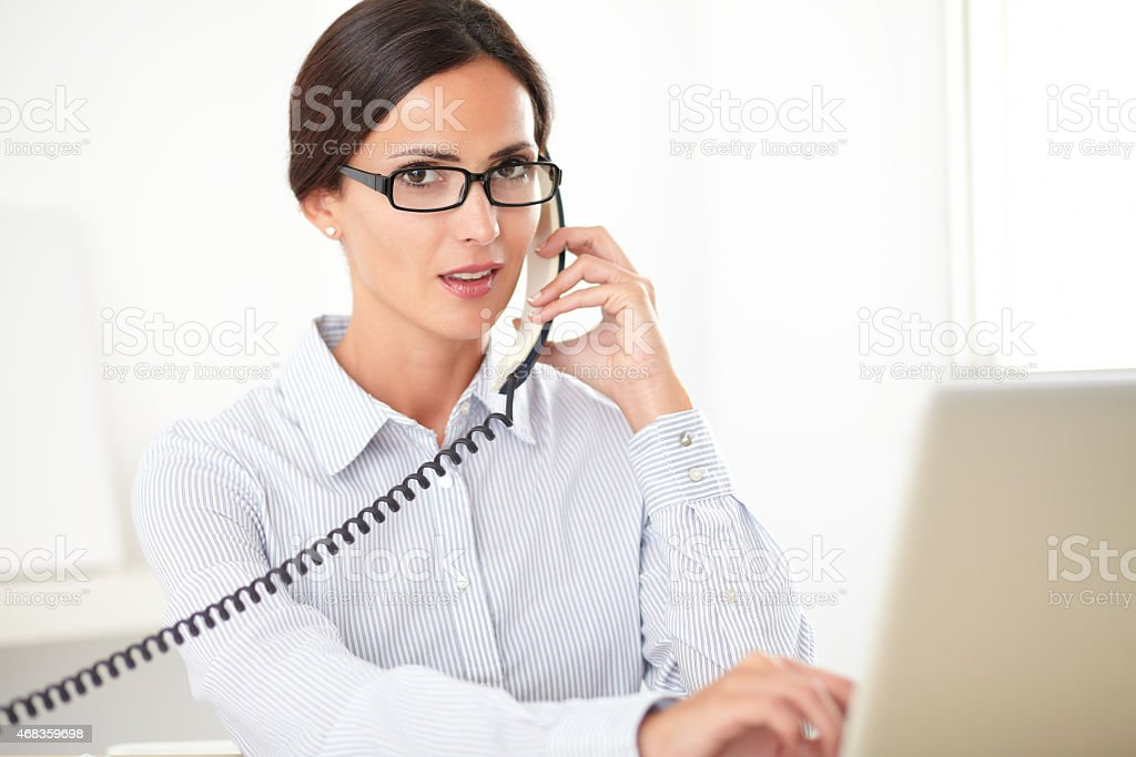 Pretty receptionist using the phone at workplace royalty-free stock photo