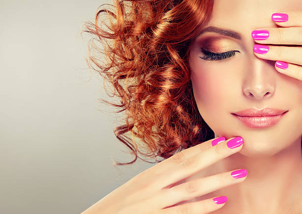 Pretty red haired girl. Pretty red haired girl with curls , fashionable makeup and pink manicure.Close up portrait.  stage make up stock pictures, royalty-free photos & images