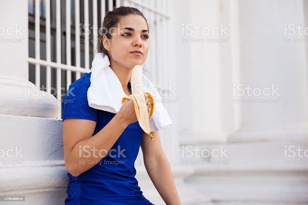 Pretty runner eating a banana bildbanksfoto