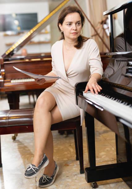 hübsche verkäuferin im piano-plattenladen - klavier verkaufen stock-fotos und bilder