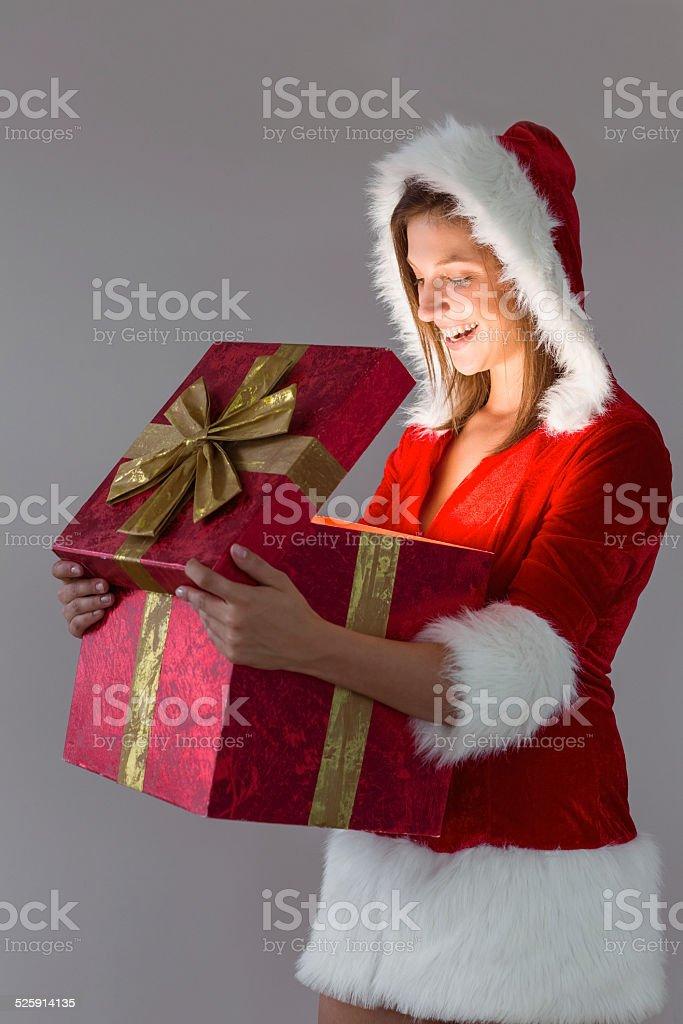 Hübsches Santa Mädchen öffnen Ein Geschenk Stockfoto Und