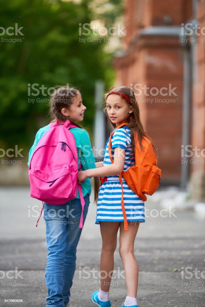 Pretty school girls walking together stock photo