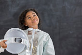 African American elementary schoolgirl dresses as an astronaut for career day at school. She is looking up and standing in front of a chalkboard.