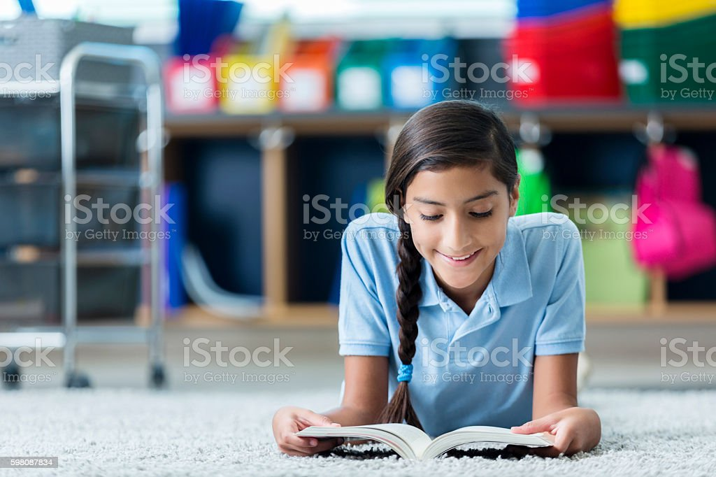 Pretty schoolgirl reads book in library – Foto