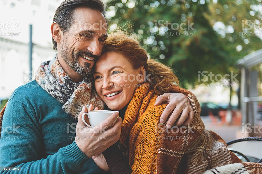 Pretty senior lovers hugging with joy stock photo