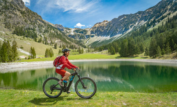 pretty senior woman on electric mountain bike pretty senior woman riding her electric mountain bike at the Seealp lake in the Nebelhorn area above  Oberstdorf, Allgau Alps, Bavaria, Germany  Electric bike stock pictures, royalty-free photos & images