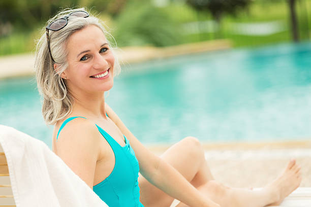 Pretty senior woman relaxes beside swimming pool Pretty Caucasian senior woman relaxes in lounge chair beside community swimming pool. She is wearing a turquoise swim suit and sunglasses. alongside stock pictures, royalty-free photos & images