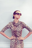 Fashion and people concept - pretty sexy woman in leopard dress and sunglasses posing outdoors in urban style on against the gray wall