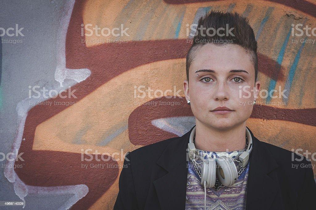 Pretty short hair girl posing against a wall stock photo