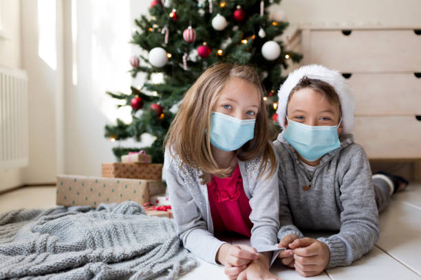 Pretty siblings lying in front of a Christmas tree celebrating Christmas during corona crisis lockdown stock photo