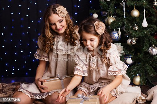 1061876006istockphoto Pretty sisters are sharing gifts near christmas tree 502327348