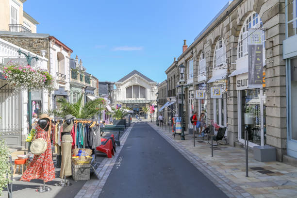 Pretty small traffic free street with shops putting out their stock on the street to attract buyers into their businesses stock photo