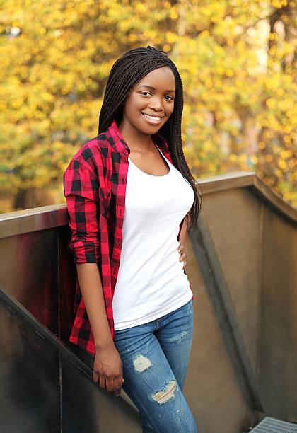 schönen lächeln afrikanischen frau in ein rot kariertes hemd - rote dreads stock-fotos und bilder