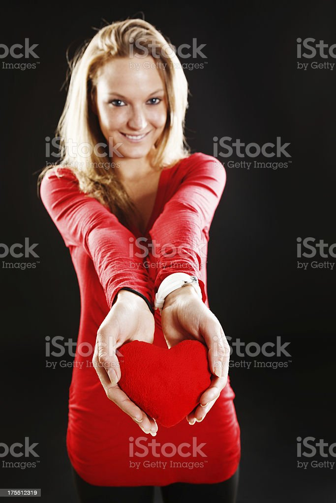 Pretty, smiling blonde offers her heart stock photo
