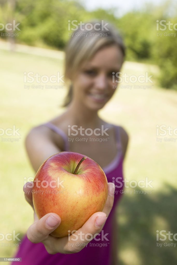 Pretty Smiling Caucasian Woman Holding Out an Apple royalty-free stock photo