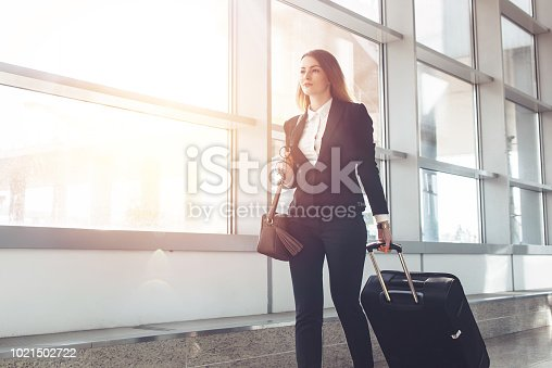 Pretty smiling female flight attendant carrying baggage going to airplane in the airport.
