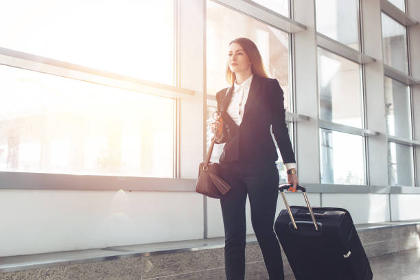 Pretty smiling female flight attendant carrying baggage going to airplane in the airport stock photo
