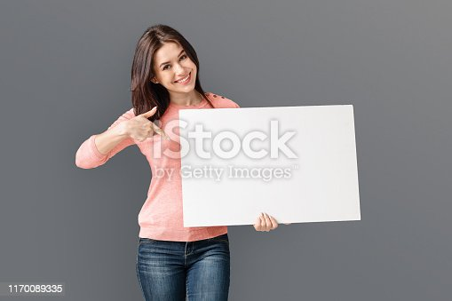 1168002879 istock photo Pretty smiling girl is holding white advertising board 1170089335