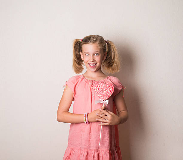 pretty smiling girl with big heart shaped lollipop - pigtails stock photos and pictures