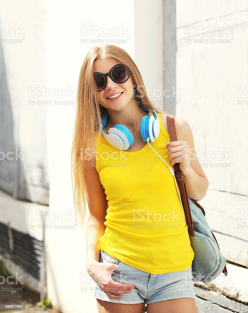 Bella Ragazza sorridente con le cuffie e zaino in città foto stock  royalty-free 9a90a9f2fba9