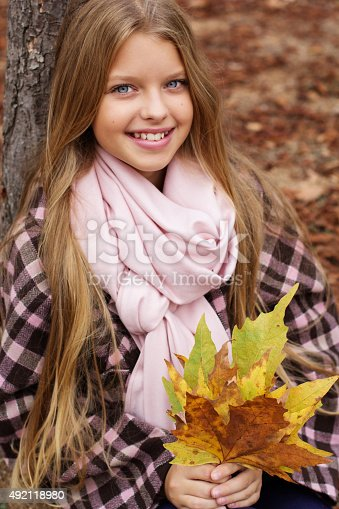 istock Pretty smiling girl with maple leaves in hands 492118980
