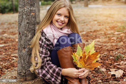 istock Pretty smiling girl with maple leaves in hands 492118996