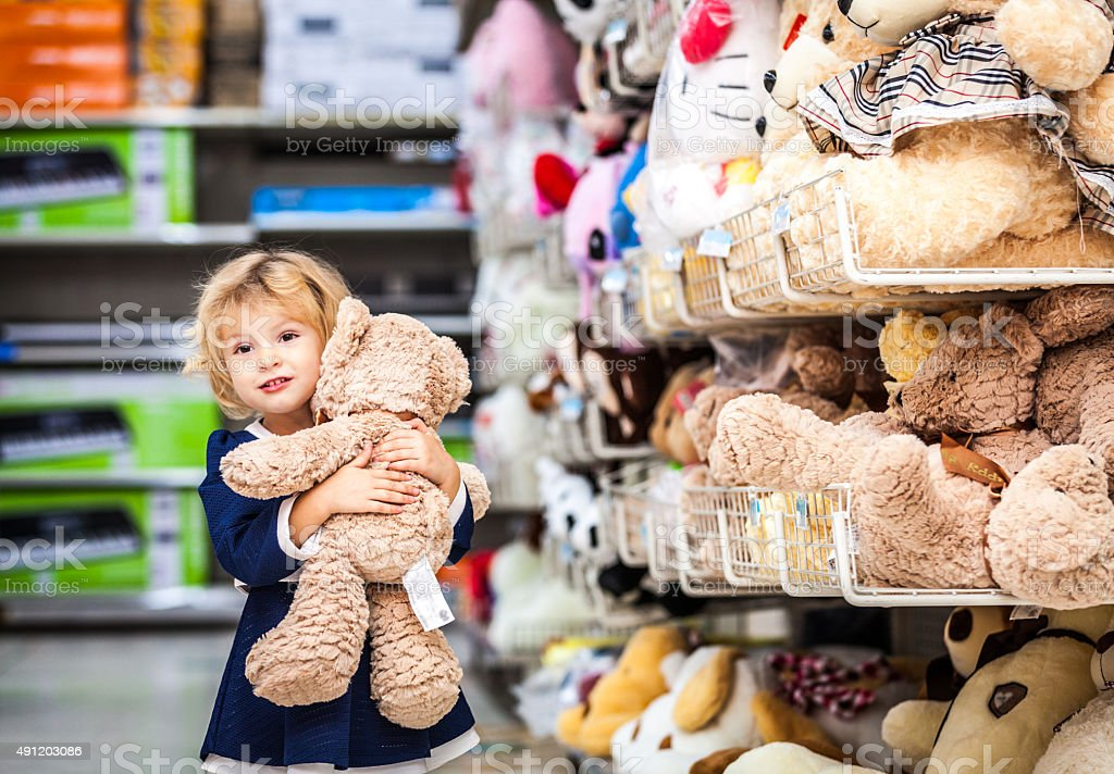 Pretty smiling little girl with teddy-bear in grocery store stock photo