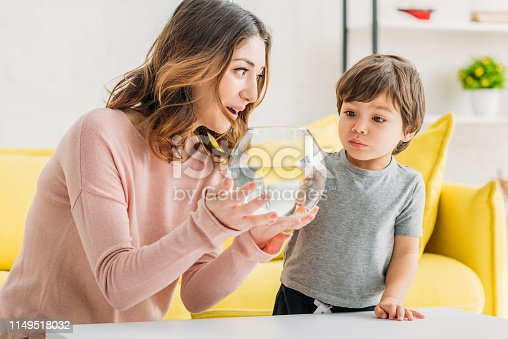109350576 istock photo pretty smiling mother showing fish bowl to adorable son 1149518032