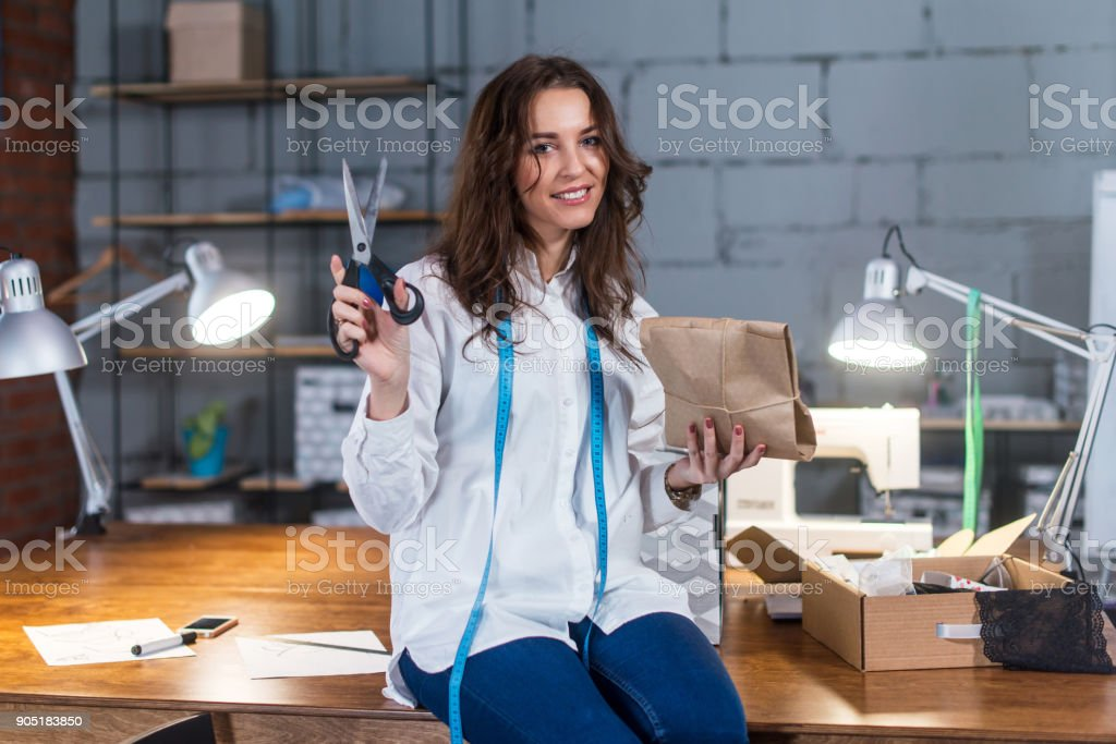 Pretty smiling seamstress sitting on table packing presents in craft paper holding scissors in modern tailor s shop stock photo