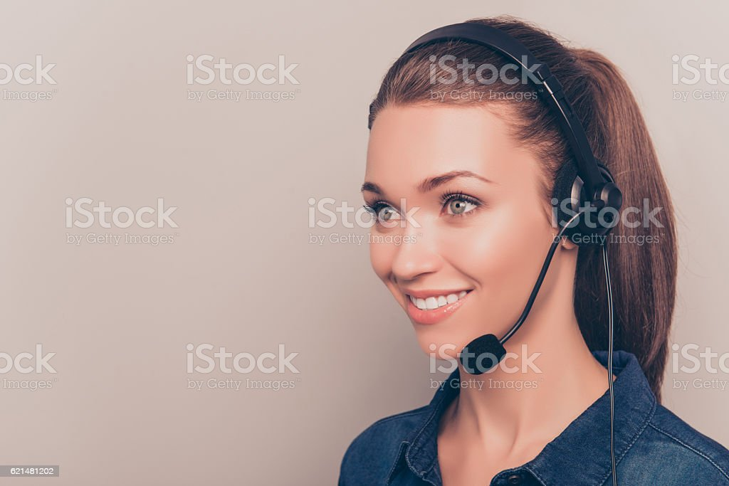 Pretty smiling secretary  in headphones isolated on gray background stock photo