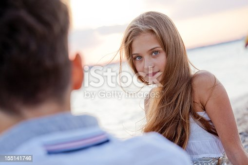 91482522 istock photo Pretty smiling teenage girl with guy on summer sea beach 155141746
