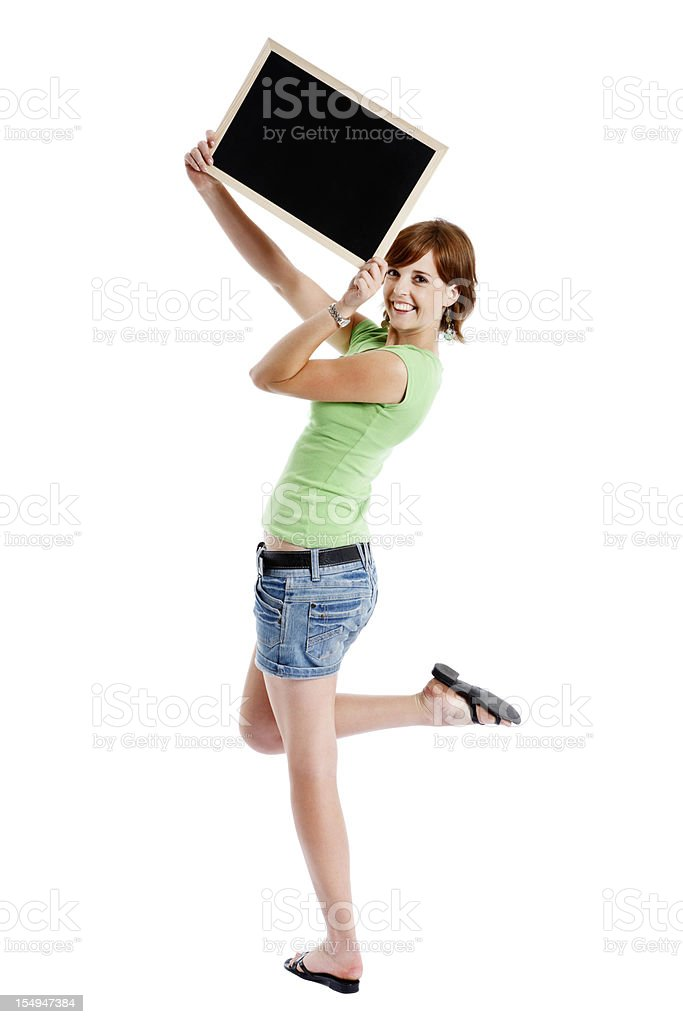 Pretty, smiling woman holds up blank blackboard royalty-free stock photo