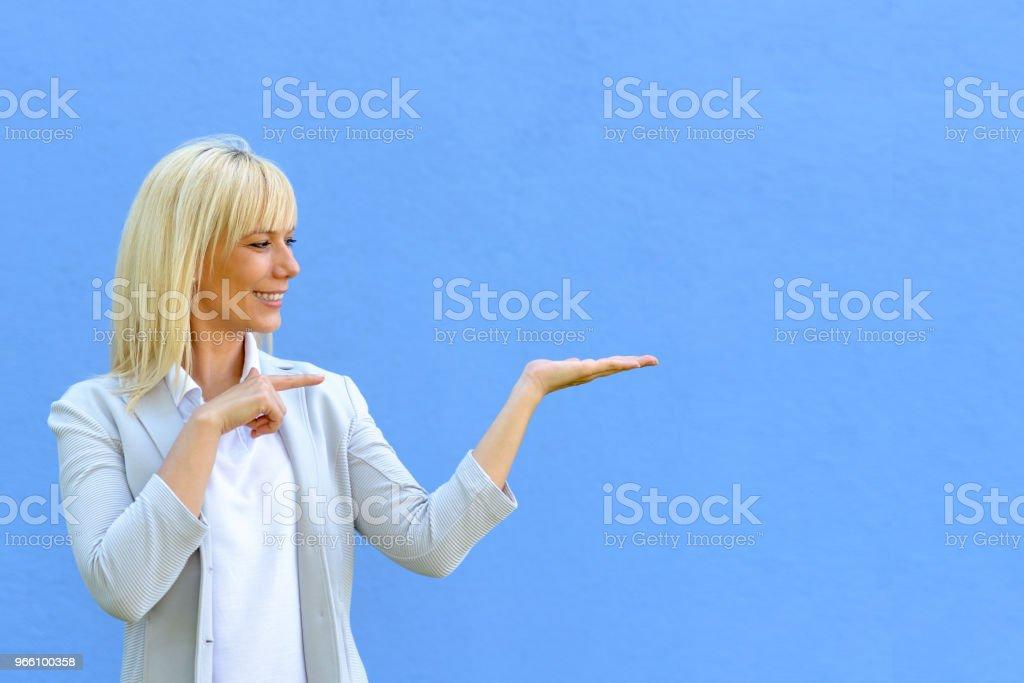 Ganska leende kvinna som pekar på hennes tomma hand - Royaltyfri Affischtavla Bildbanksbilder