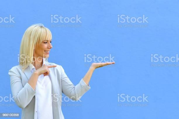 Ganska Leende Kvinna Som Pekar På Hennes Tomma Hand-foton och fler bilder på Affischtavla
