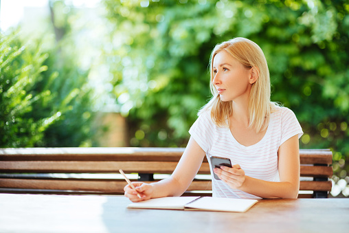 818512928 istock photo Pretty smiling young woman drawing a sketches. 1015038862