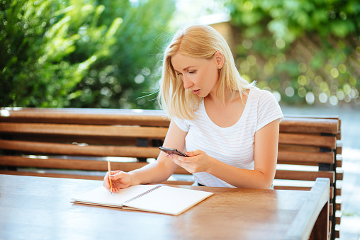 818512928 istock photo Pretty smiling young woman drawing a sketches. 1017067810