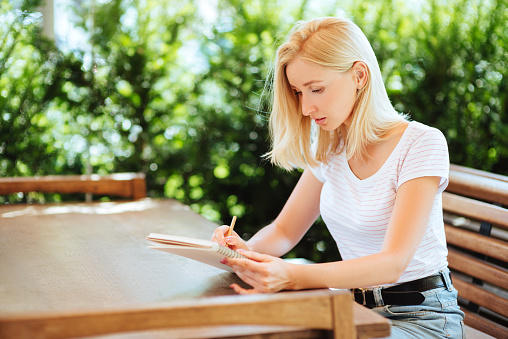 818512928 istock photo Pretty smiling young woman drawing a sketches. 1024652988