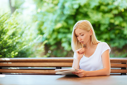 818512928 istock photo Pretty smiling young woman drawing a sketches. 1041473850