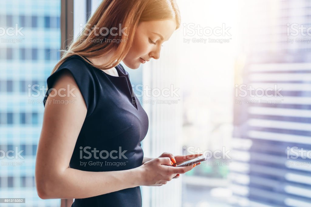 Pretty smilingwoman using smartphone standing in office stock photo