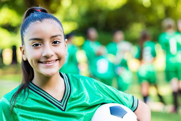 Pretty soccer player holding the ball with her team Pretty hispanic girl with her hair tight in a ponytail. She is smiling directly at the camera. Her teammates are in the background. She is wearing a bright green soccer uniform. Her teammates are also wearing the same brightly colored soccer uniforms. They are blurry in the background, behind her. cute middle school girls stock pictures, royalty-free photos & images