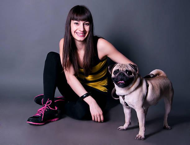 schöne sport mädchen mit einem mops hund im studio - hunde strumpfhosen stock-fotos und bilder