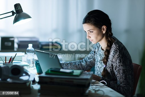 istock Pretty student doing homework 512058184