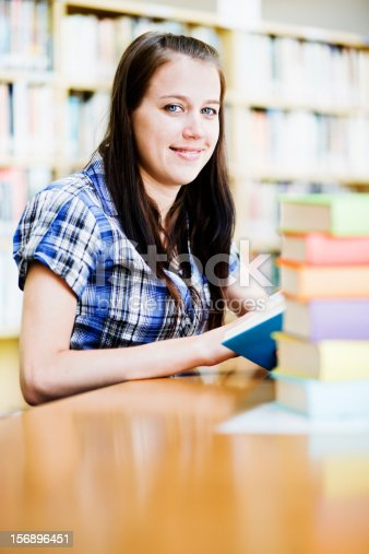 521911045istockphoto Pretty student looks up from studying in the library 156896451
