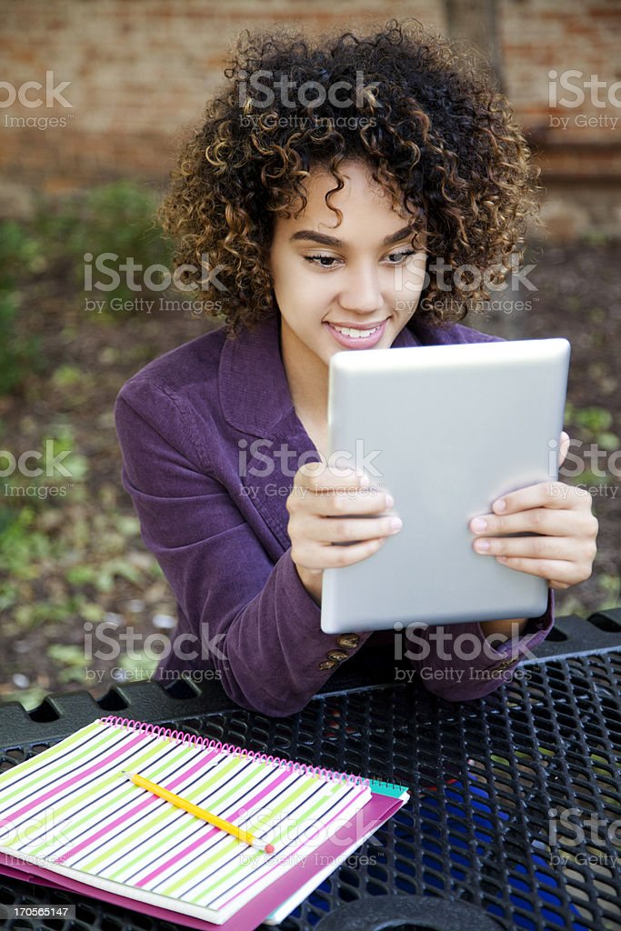 Pretty student reading a digital tablet royalty-free stock photo