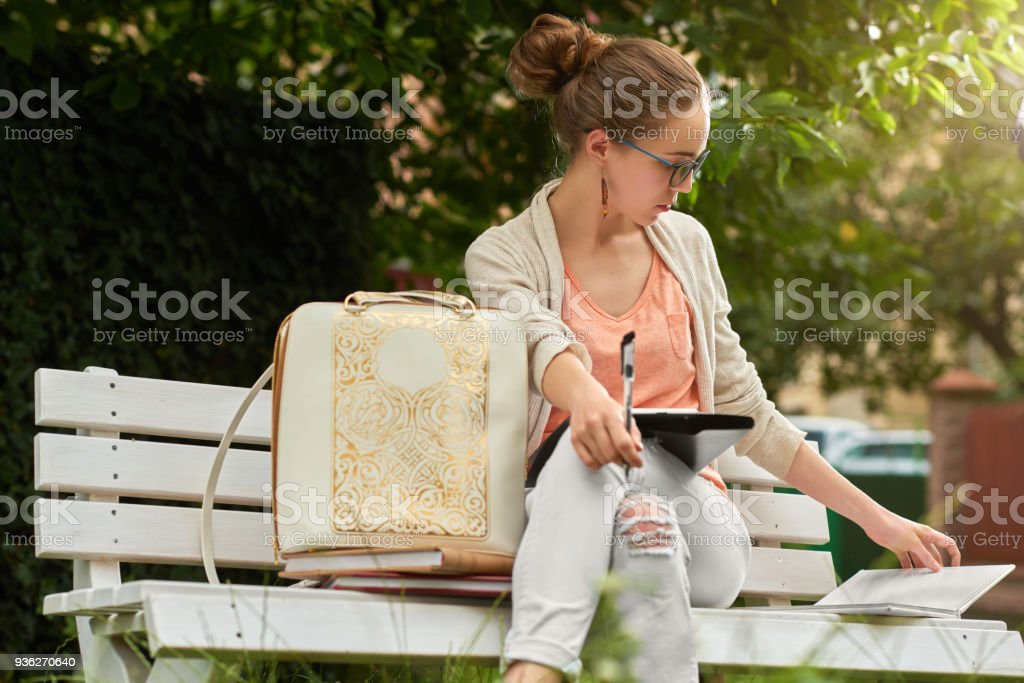 Pretty student studies on a white bech in a city park stock photo
