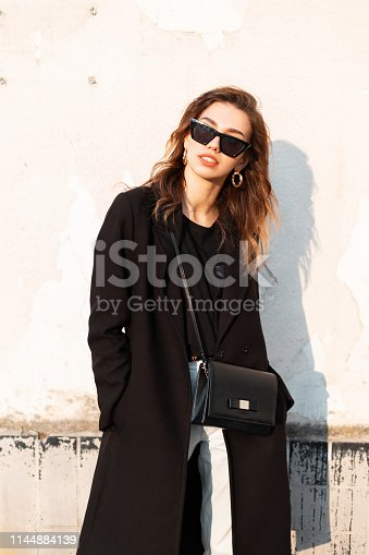 Pretty stylish hipster young woman in dark sunglasses in a vintage long coat in white jeans with a black handbag stands near a white wall on a bright sunny day. Attractive girl enjoys the sunshine.