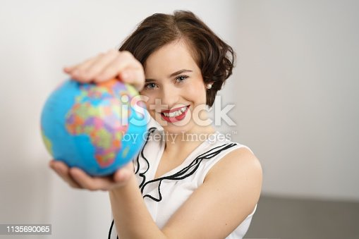 Pretty stylish young woman holding a world globe extended to the camera in a concept of travel or saving the planet, with focus to her face