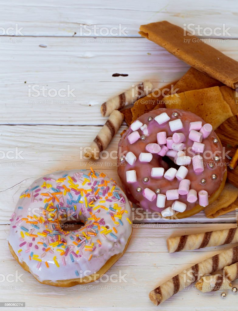pretty tasty donuts on white wooden background royalty-free stock photo