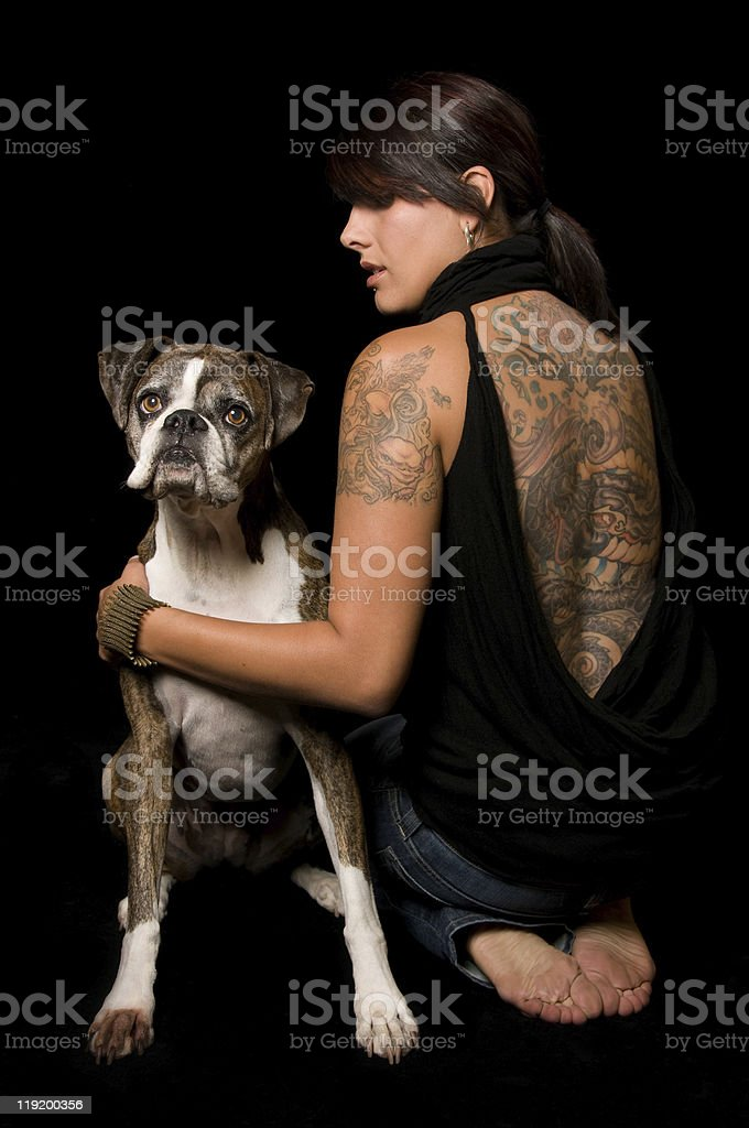 Pretty Tattooed Woman Hugging Boxer Dog stock photo